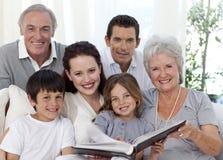 Famille de sourire regardant un album de photographie Photographie stock libre de droits