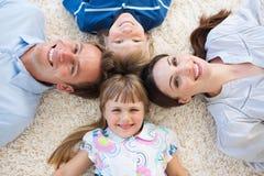 Famille de sourire se situant en cercle sur l'étage Photographie stock libre de droits
