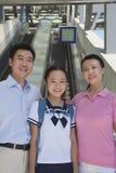Famille de sourire se tenant à côté de l'escalator près de la station de métro regardant l'appareil-photo, portrait Images libres de droits