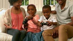 Famille de sourire sur le sofa avec des enfants jouant des jeux vidéo banque de vidéos