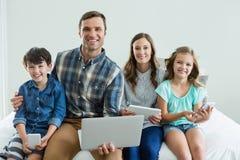 Famille de sourire utilisant l'ordinateur portable, le comprimé numérique et le téléphone portable dans la chambre à coucher Photographie stock libre de droits