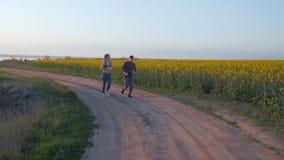 Famille de sports, jeunes athlètes homme et fille avec des tresses de kanekalon courues autour sur la nature sur le gisement de c clips vidéos