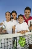 Famille de tennis au filet sur la fille de court de tennis tenant le portrait de trophée photo stock