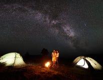 Famille de touristes avec la fille ayant un repos en montagnes la nuit sous le ciel étoilé avec la manière laiteuse Photographie stock libre de droits