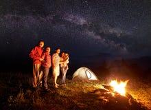 Famille de touristes avec la fille ayant un repos en montagnes la nuit sous le ciel étoilé avec la manière laiteuse images stock