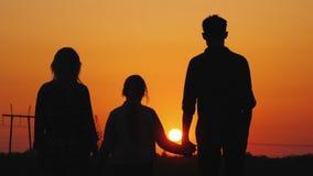 Famille de trois admirant le coucher du soleil orange au-dessus de la ville, vue arrière photo stock