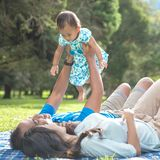 Famille de trois avec des happines de bébé s'étendant sur une herbe Photos libres de droits