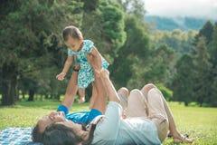 Famille de trois avec des happines de bébé s'étendant sur une herbe Photo libre de droits
