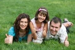 Famille de trois avec des pouces vers le haut en stationnement Photo stock