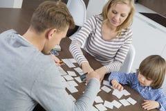 Famille de trois cartes jouantes à la maison Photo libre de droits
