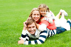 Famille de trois de sourire empilée sur l'un l'autre photos stock