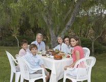 Famille de trois générations à la table de salle à manger de jardin Photos stock