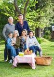 Famille de trois générations appréciant le pique-nique en parc Photo libre de droits