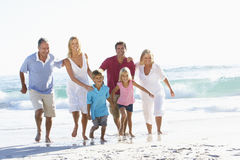 Famille de trois générations en vacances fonctionnant le long de la plage photographie stock libre de droits