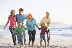 Famille de trois générations en vacances fonctionnant le long de la plage image stock