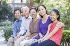 Famille de trois générations se reposant dans leur cour d'appartement Photographie stock