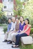 Famille de trois générations se reposant dans leur cour d'appartement Photographie stock libre de droits