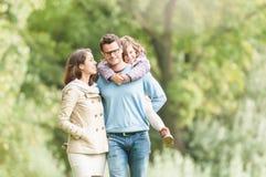 Famille de trois heureuse ayant l'amusement extérieur. Photos stock