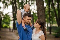 Famille de trois heureuse Le père garde le fils sur des épaules Relations de concept et temps libre insouciant Photo stock