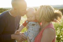 Famille de trois heureuse Père, mère et bébé jouant dehors en été au temps de coucher du soleil Photographie stock