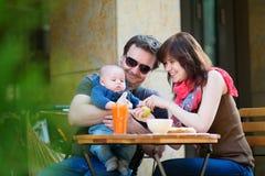Famille de trois heureuse prenant le petit déjeuner Image libre de droits