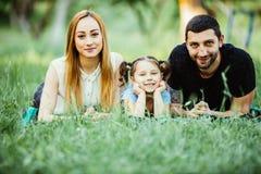 Famille de trois heureuse se trouvant sur l'herbe Concept des relations de famille heureuses et de temps libre insouciant Photos libres de droits