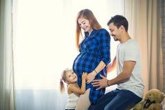 Famille de trois Maman enceinte, papa et petite fille Images stock