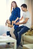 Famille de trois Maman enceinte, papa et petite fille Photographie stock