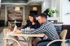 Famille de trois ordinaire avec la petite mère de fille et de père donnant la consolation au café pendant le déjeuner images libres de droits