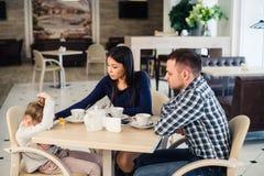 Famille de trois ordinaire avec la petite mère de fille et de père donnant la consolation au café pendant le déjeuner photo libre de droits
