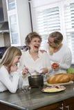 Famille de trois rétablissements dans la cuisine faisant cuire le déjeuner Images libres de droits