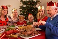 Famille de trois rétablissements appréciant le repas de Noël Photo stock