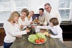 Famille de trois rétablissements dans la cuisine faisant cuire le déjeuner Photo stock