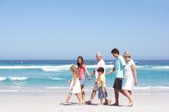 Famille de trois rétablissements marchant le long de la plage sablonneuse Photos stock