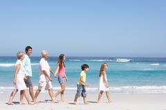 Famille de trois rétablissements marchant le long de la plage sablonneuse Images stock