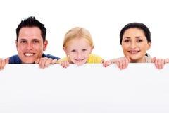 Famille derrière le panneau blanc Image stock