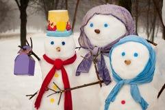 Famille des bonhommes de neige dehors Photo stock