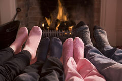 Famille des pieds réchauffant à une cheminée Images stock