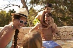 Famille des vacances ayant l'amusement par la piscine extérieure image stock