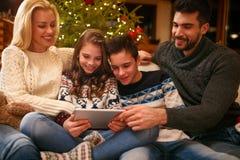Famille des vacances de Noël regardant des photos sur le comprimé Photos libres de droits