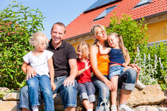 Famille devant la maison ou la maison Photos libres de droits