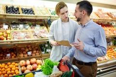 Famille discutant la liste d'achats dans le supermarché photos stock