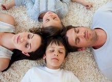Famille dormant sur l'étage avec des têtes ensemble Images stock
