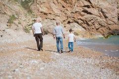Famille du père première génération et du fils sur une plage rocheuse des vacances appréciant le temps ensemble Photos stock
