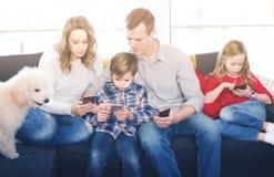 Famille du temps quatre passant jouant avec des smartphones Images libres de droits