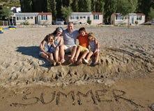 Famille embrassé sur la plage en été   Photos stock