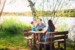 Famille en été sur un pique-nique près d'un étang, l'eau Vacances de famille en nature Une petite fille alimente son père Image libre de droits
