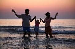 Famille en mer contre le coucher du soleil Images libres de droits