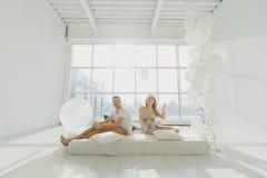 Famille enceinte heureuse avec un petit fils, jouant contre la fenêtre dans une salle blanche Photos libres de droits