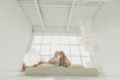 Famille enceinte heureuse avec un petit fils, jouant contre la fenêtre dans une salle blanche Photographie stock